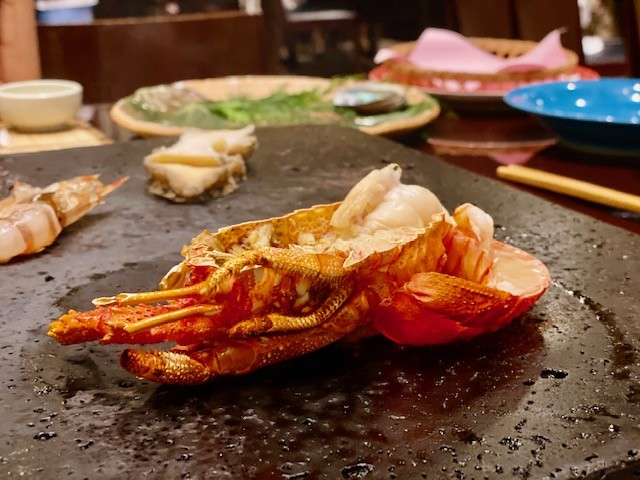 half lobster, still in its shell, cooked right at the table, at Mokushundo, a traditional Japanese restaurant at Chinzanso in Tokyo,