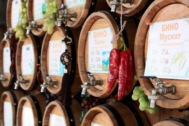 Wooden wine barrels, grapes and red hot chili peppers on the market